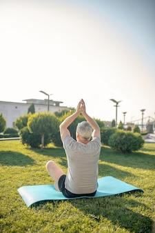 Rückansicht des grauhaarigen mannes, der draußen yoga praktiziert und hände über kopf hebt
