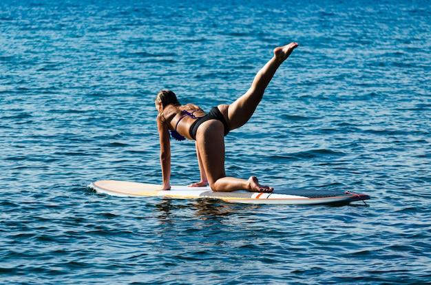 Rückansicht des heißen mädchens, das yoga auf stand up paddle board tut.