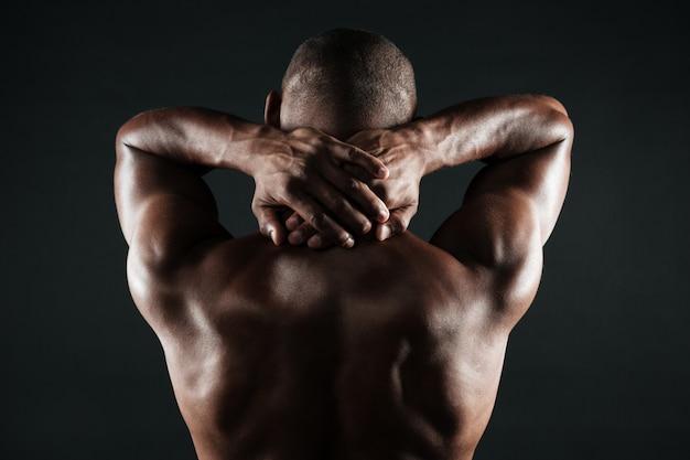 Rückansicht des jungen afrikanischen mannes mit dem muskulösen körper, der seinen hals hält