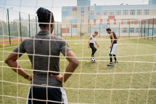 Rückansicht des jungen afrikanischen sportlers, der durch netz steht und zwei spieler mit fußball auf dem feld betrachtet