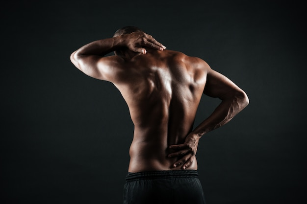 Rückansicht des jungen afrikanischen sportmannes, der schmerz in seinem rücken fühlt