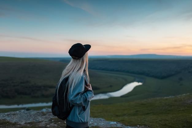 Rückansicht des jungen blonden mädchens mit rucksack, der sonnenuntergang auf gipfel der hügel genießt. reisekonzept.