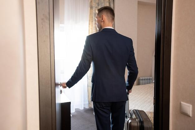 Rückansicht des jungen eleganten geschäftsreisenden in der abendgarderobe, der am morgen bequemes hotelzimmer betritt