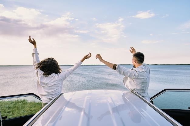 Rückansicht des jungen fröhlichen paares in den hemden, die nah an ihrem auto mit offenen türen stehen und freude an der freiheit mit erhobenen händen ausdrücken