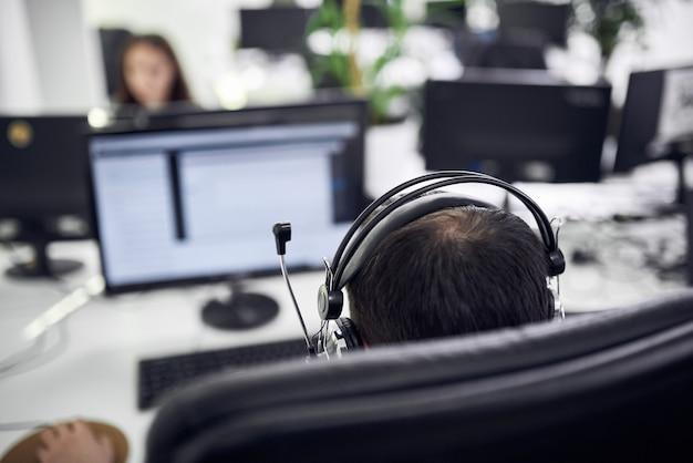 Rückansicht des jungen geschäftsmannes, der kopfhörer am computertisch im modernen büro trägt