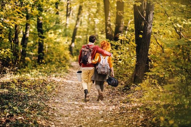 Rückansicht des jungen glücklichen paares in der liebe, die an einem schönen herbsttag in der natur umarmt und geht. paar hält picknickausrüstung.