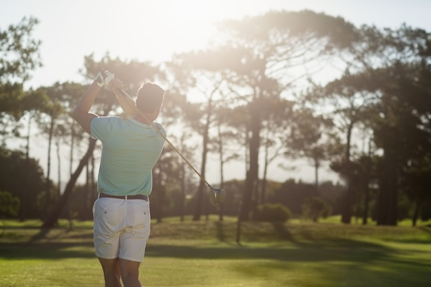 Rückansicht des jungen golfers, der schuss nimmt