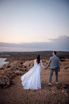 Rückansicht des jungen hochzeitspaares, der braut und des bräutigams, die am abend auf zypern an einem felsigen strand spazieren gehen?