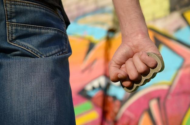 Rückansicht des jungen kaukasischen mannes mit messingknöchel auf seiner hand gegen ghetto-backsteinmauer