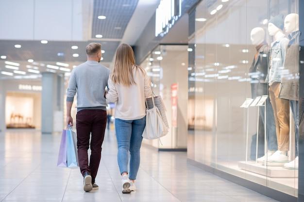 Rückansicht des jungen lässigen paares, das sich entlang des schaufensters im einkaufszentrum bewegt, während es es verlässt, nachdem es gekauft hat, was sie wollten