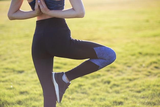 Rückansicht des jungen mädchens in der yoga-position meditiert im feld bei sonnenaufgang.