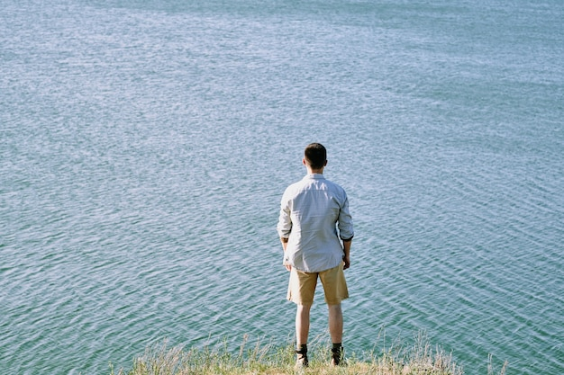 Rückansicht des jungen männlichen reisenden im hemd und in den shorts, die am flussufer nahe am wasser stehen und natur und einsamkeit am sommertag genießen