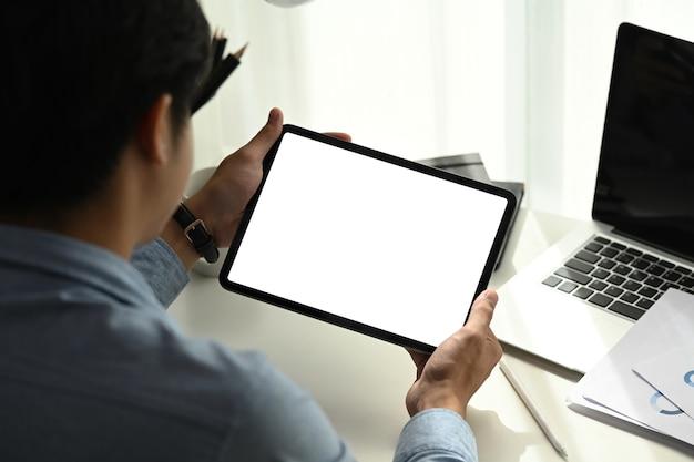 Rückansicht des jungen mannes, der an tragbarem elektronischem gerät des tablets arbeitet und nach informationsdokumenten im internet sucht.