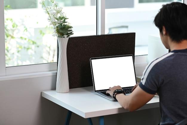 Rückansicht des jungen mannes, der freiberuflich mit laptop arbeitet, während er in einem modernen zuhause sitzt.