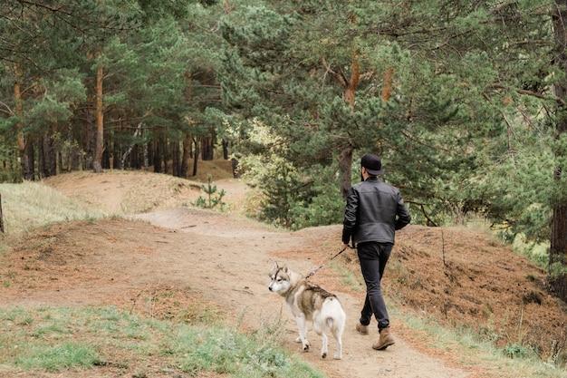 Rückansicht des jungen mannes, der leine des niedlichen reinrassigen huskyhundes hält, während beide in ländlicher umgebung abkühlen