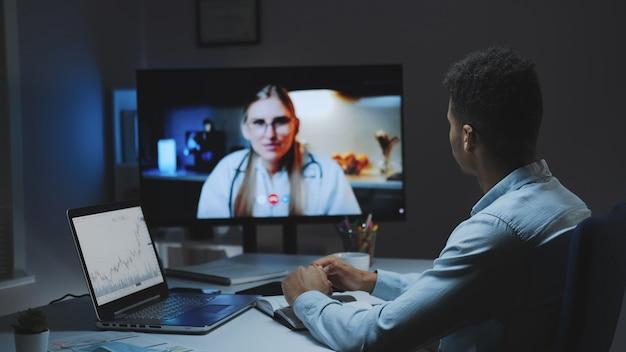Rückansicht des jungen mannes, der videoanruf mit chefarzt über ihre gesundheit macht
