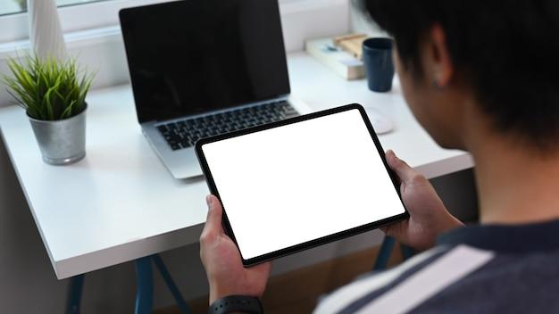 Rückansicht des jungen mannes, der vor laptop sitzt und digitales tablett im heimbüro verwendet.
