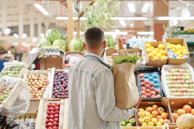 Rückansicht des jungen mannes in der leichten jeansjacke, die papiertüte hält und saftige früchte am bauernmarkt wählt