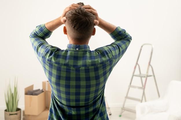 Rückansicht des jungen mannes verwirrt mit dem renovierungsproblem, das den kopf in der hand hält, während man den leeren raum mit beweglichem zeug betrachtet