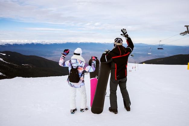 Rückansicht des jungen paares, das snowboards hält und mit den händen oben im verschneiten winter auf der spitze des berges genießt.