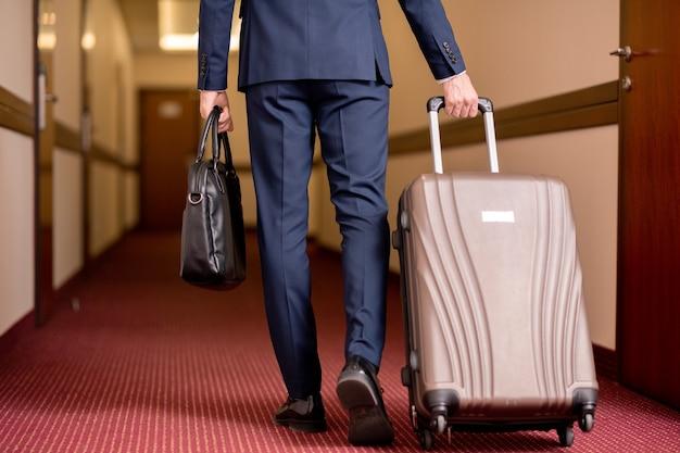 Rückansicht des jungen reisenden geschäftsmannes im anzug, der schwarze lederhandtasche trägt und koffer zieht, während entlang korridor bewegt