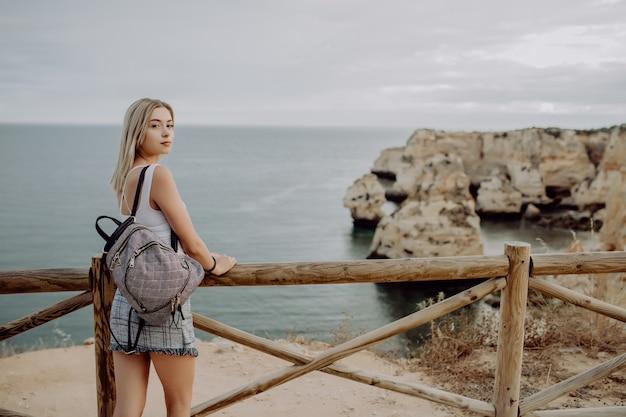Rückansicht des jungen schönen weiblichen reisenden, der sonnenuntergang und schöne seelandschaft mit einem aussichtspunkt betrachtet.