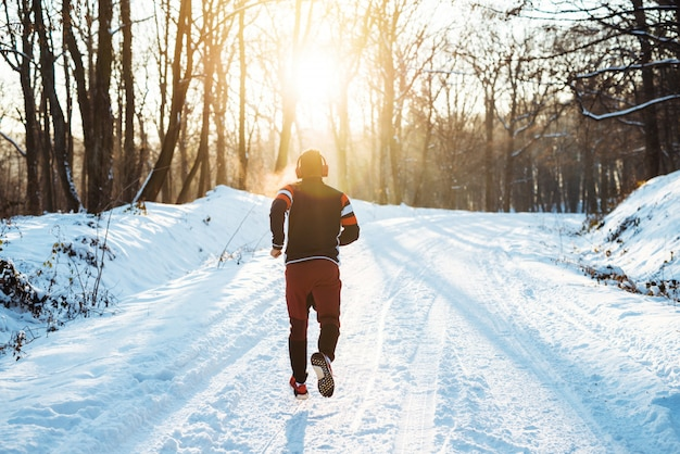 Rückansicht des jungen sportlichen läufers in der sportbekleidung mit kopfhörern, die am morgen im winterlichen wald laufen.