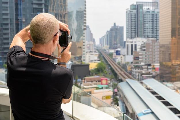 Rückansicht des kahlen älteren touristenmannes, der fotos der ansicht macht