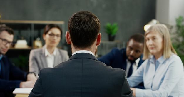 Rückansicht des kaukasischen mannes, der konferenz von partnern und investoren am schreibtisch im büro läuft.