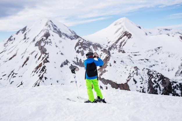 Rückansicht des kleinen jungen mit rucksack und ski, der ein foto im verschneiten winter auf der spitze des berges macht.
