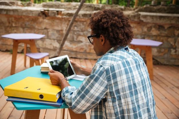 Rückansicht des konzentrierten jungen mannes, der sitzt und tablette am tisch verwendet