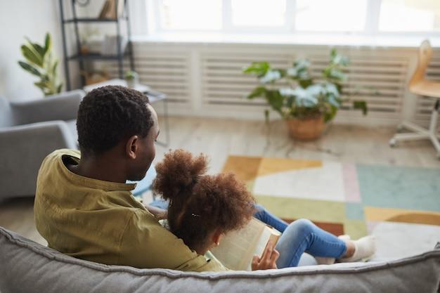 Rückansicht des liebevollen afroamerikanischen vaters und seiner tochter, die zusammen auf der couch in gemütlichem interieur sitzen, kopierraum