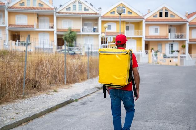 Rückansicht des lieferboten, der gelbe thermotasche trägt. professioneller kurier, der auf der straße geht und bestellung zu fuß liefert.