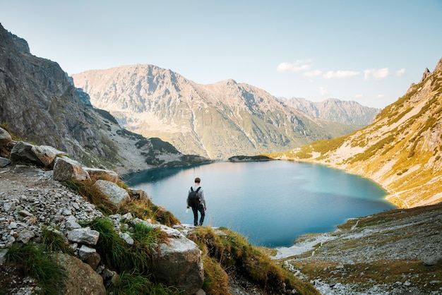 Rückansicht des männlichen touristen mit rucksackwandern auf bergen in der nähe des morskie oko-sees