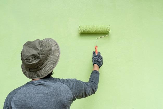 Rückansicht des malers der jungen männer im t-shirt und in den handschuhen, die eine wand mit farbroller malen.