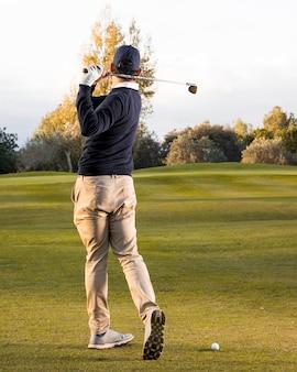 Rückansicht des mannes, der auf dem grasbewachsenen golffeld spielt