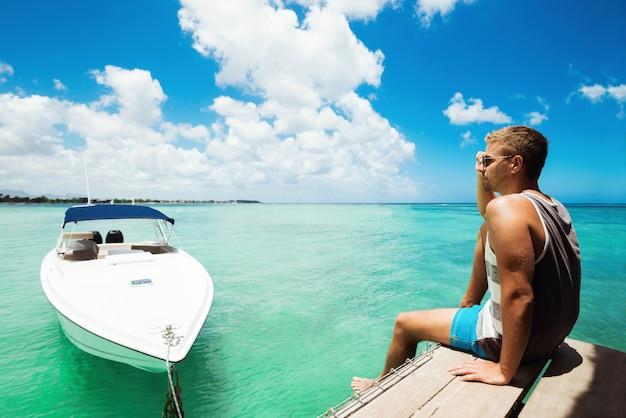 Rückansicht des mannes, der auf pier sitzt, der bereit ist zu segeln
