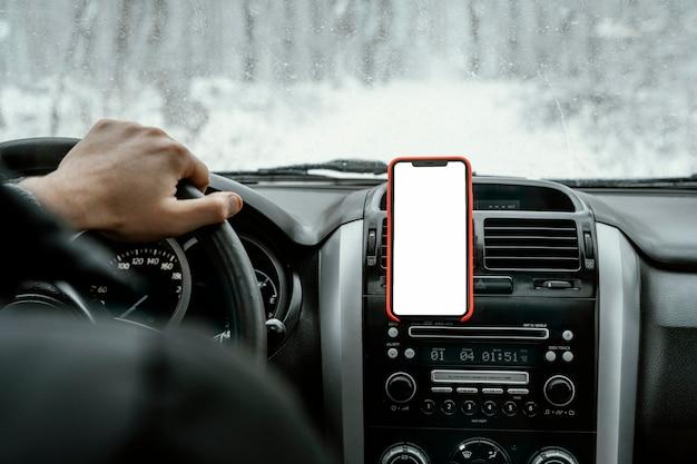Rückansicht des mannes, der das auto für auf einer straßenreise mit smartphone fährt