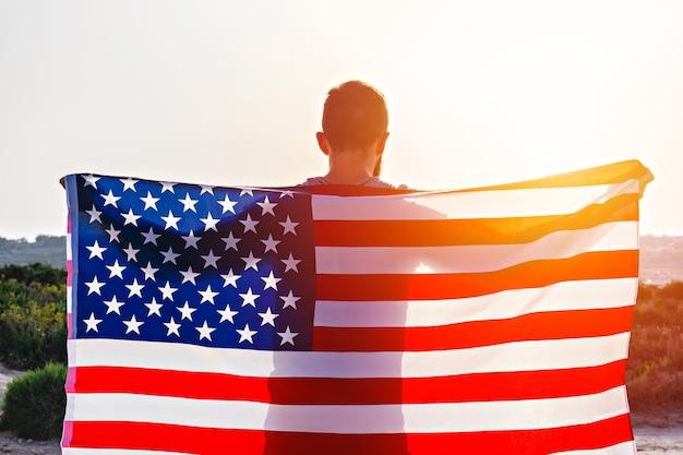Rückansicht des mannes, der die amerikanische flagge der usa gegen den sonnenunterganghimmel im freien hält. unabhängigkeitstag der vereinigten staaten von amerika. konzept des amerikanischen patriotischen volkes