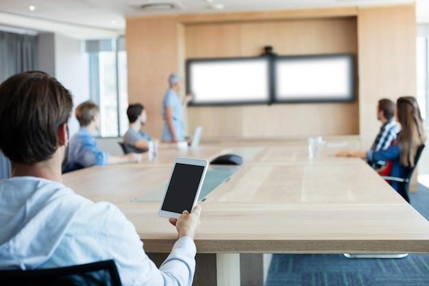 Rückansicht des mannes, der eine tablette hält, während er an einer besprechung im konferenzraum teilnimmt