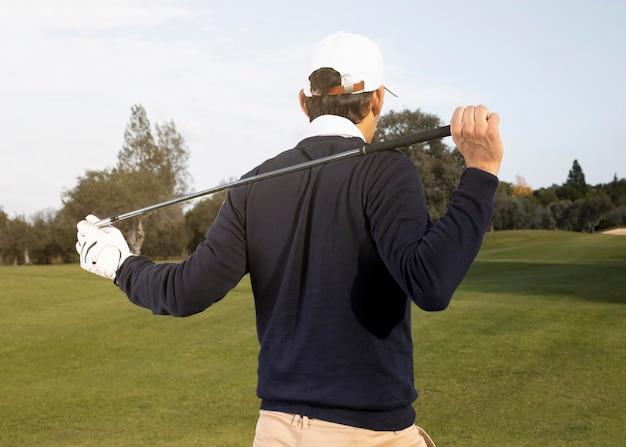 Rückansicht des mannes, der golf auf dem feld spielt