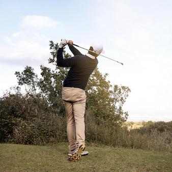 Rückansicht des mannes, der golf spielt
