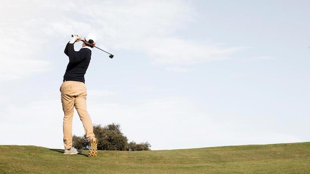 Rückansicht des mannes, der golfball auf dem feld schlägt