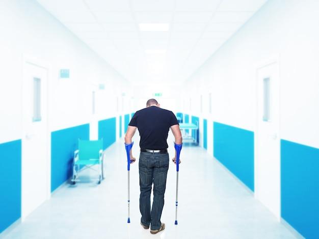 Rückansicht des mannes, der mit krücken im krankenhaus geht