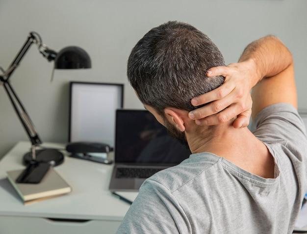 Rückansicht des mannes, der sich ausdehnt, während er von zu hause aus arbeitet