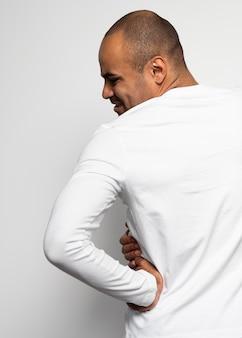 Rückansicht des mannes, der unter seitenschmerzen leidet