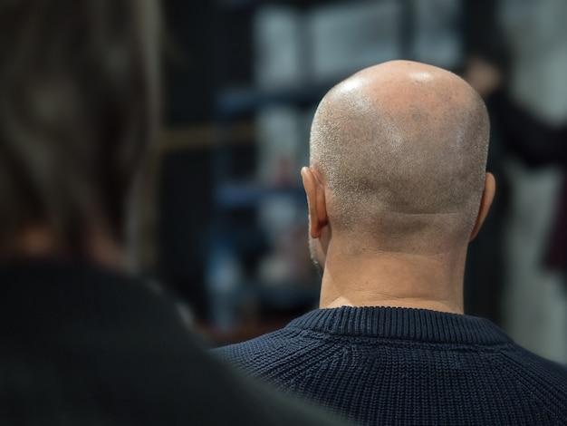 Rückansicht des mannes mit einer glatze in einem konferenzsaal.