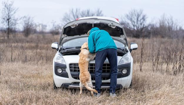 Rückansicht des mannes mit süßem hund, der auto auf dem feld repariert