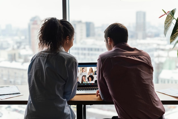Rückansicht des mannes und der frau im büro, die einen videoanruf haben