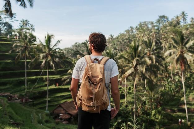 Rückansicht des mannforschers mit reiserucksack, der natürliche umgebung der plantage des grünen aufstiegs während reise in bali genießt